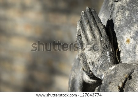 praying hands of an antique statue - stock photo