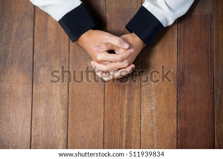 Praying hands of woman on wooden desk