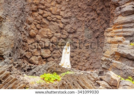 Praying Madonna in front of rock wall in Ribeira da Janela, Madeira, Portugal  - stock photo