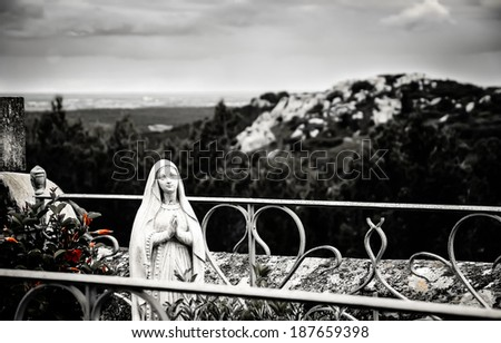 Praying Madonna statue with a rosary behind  the metal grave fence at the cemetery in Les Baux-de-Provence (Provence, France) and a beautiful landscape at backgrounds. Aged photo. Black and white, - stock photo