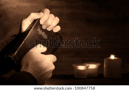 Praying man hands holding and clinching an old holy bible sacred book in a dark church during a prayer worship service with religious candles glowing in nostalgic aged sepia - stock photo
