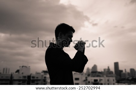 Praying man in the city - stock photo