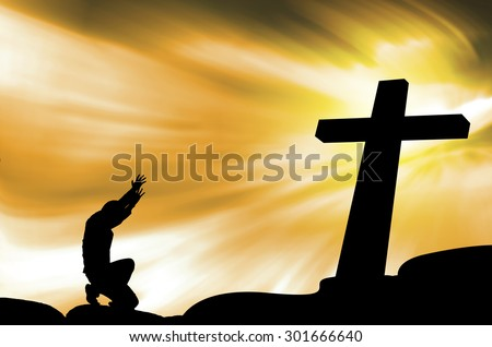praying man with black cross silhouette in rocks over a  sky