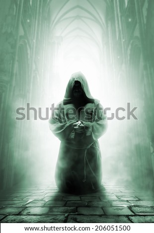 Praying medieval monk in dark temple corridor - stock photo