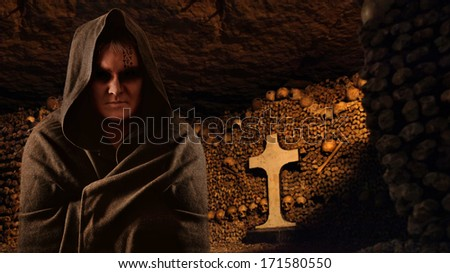 Praying monk in the dark Paris catacombs. - stock photo