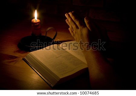 Praying next to the bible by candle light. Only light in this image is from the candle. Perfect for religious, easter or christmas themes - stock photo