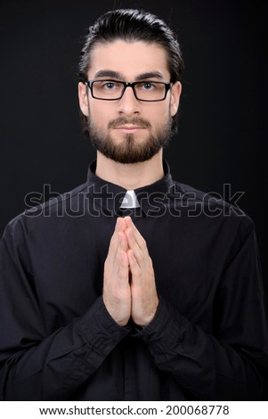 Praying priest. Portrait of priest standing isolated on black - stock photo