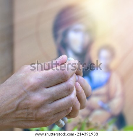 Praying with rosary in hands - stock photo