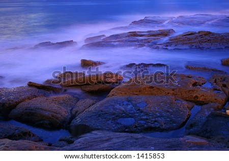 pre-dawn at the beach, water rolling in mist effect, rocks glowing,  stunning shot.