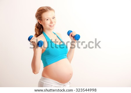 Pre-natal exercises. Beautiful pregnant woman exercising with dumbbells - stock photo