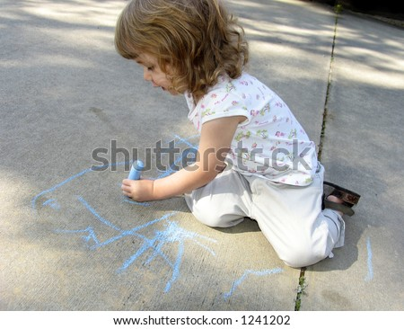 Pre-school age child drawing on sidewalk with colored chalk - stock photo