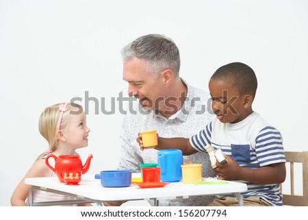 Pre School Children Enjoying Tea Party With Teacher - stock photo