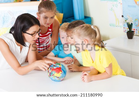 Pre-school children in the classroom with a teacher - stock photo