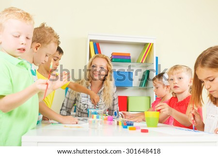 Pre-school children in the classroom with their teacher - stock photo