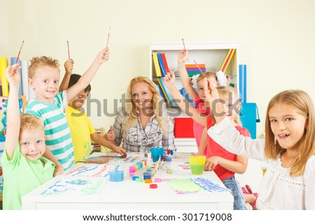 Pre-school children showing unity with teacher - stock photo