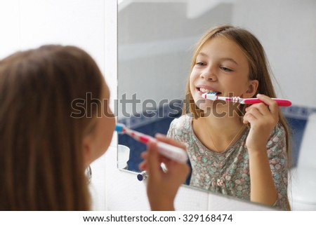 Pre teen girl brushes her teeth in the hotel bathroom - stock photo