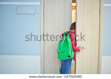 Pre-teen schoolboy late for lesson looking into classroom - stock photo