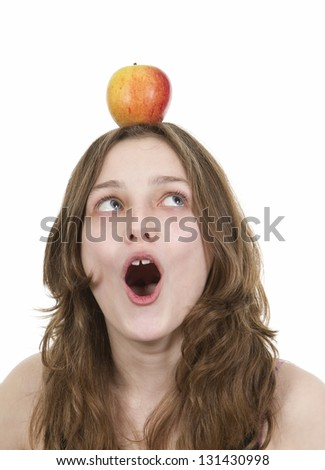 Pre teen young girl balancing an apple on her head on white background - stock photo