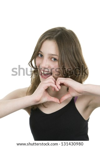 Pre teen young girl making a heart symbol with both hands on white background - stock photo