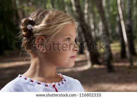 Pre-teenage girl  posing in a birch forest - stock photo