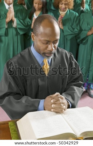 Preacher by altar in church Bowing Head in Prayer, high angle view - stock photo