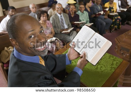 Preacher Holding Bible in Front of Congregation - stock photo
