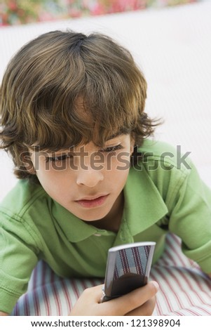 Preadolescent boy using cell phone while lying on bed - stock photo