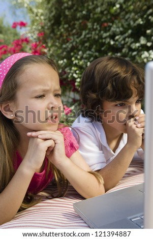 Preadolescent friends seriously looking at laptop