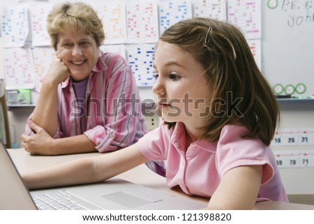 Preadolescent girl studying while teacher looking at laptop in the classroom - stock photo