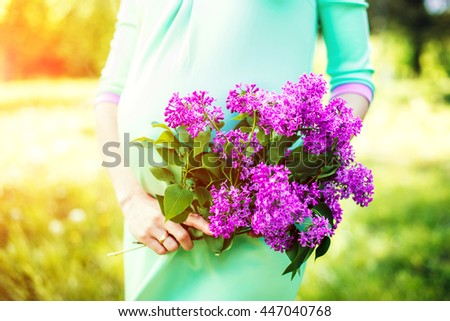 Preagnant woman in the park with flowers