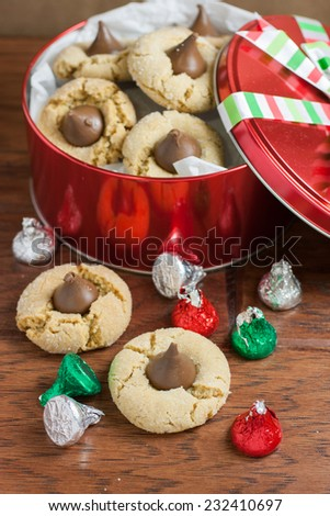 Preanut butter blossoms in a gift tin, highlighted with chocolate candies and and cookies on a wooden table.