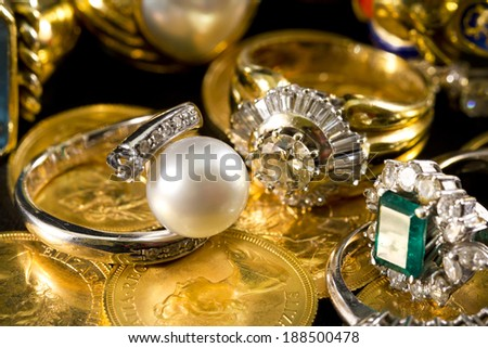 Precious jewels, rings with diamonds, emeralds and corals on pounds in gold - stock photo