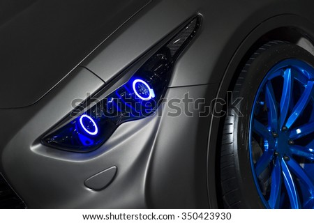 Predatory car headlight with blue lights and hood of powerful sports car with matte grey paint and wheel with blue disc - stock photo