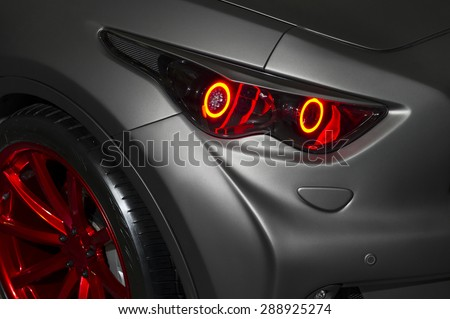 Predatory red car headlight and hood of powerful sports car with matte grey paint and wheel with red disc  - stock photo