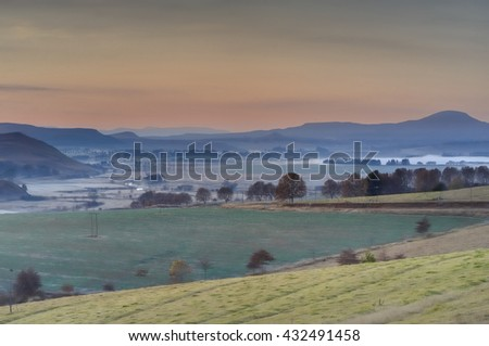 Predawn winter view of farmlands on the Umzimkulu river valley. Rising mist and frost hugs the riverside fields. Underberg, South Africa.  - stock photo