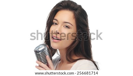 Preety woman with long brown hair standing singing into a microphone and looking seductively at the camera, over white - stock photo