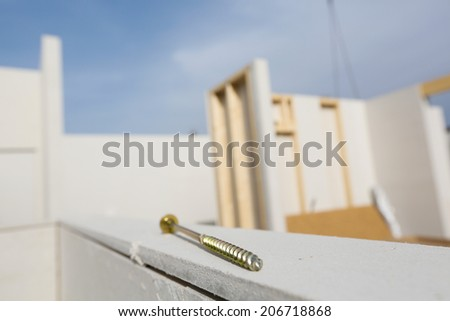 Prefabricated house in the making with screw in foreground - stock photo