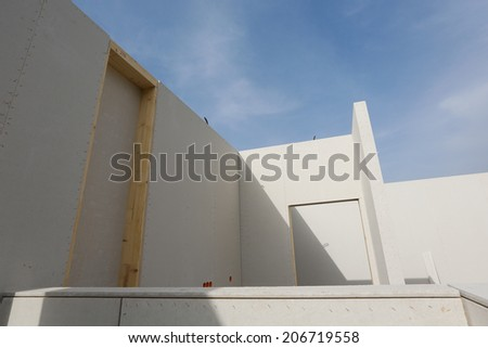 Prefabricated roofless house in the making with blue sky - stock photo
