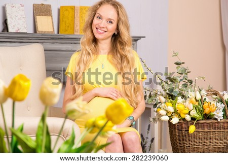 Pregnancy. Beautiful young blond woman is expecting a baby, she was pregnant. Pregnant woman in a yellow dress in a light room with flowers. Woman's happiness. Mom expecting baby. Maternity concept. - stock photo
