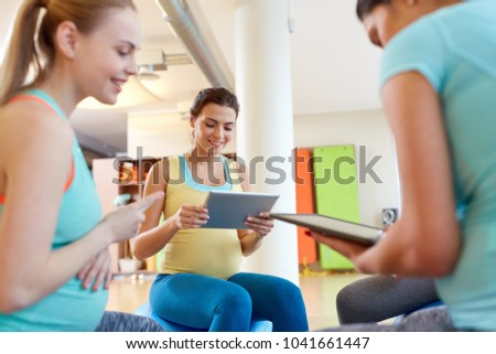 pregnancy, fitness and technology concept - group of happy pregnant women with tablet pc computers sitting on exercise balls in gym