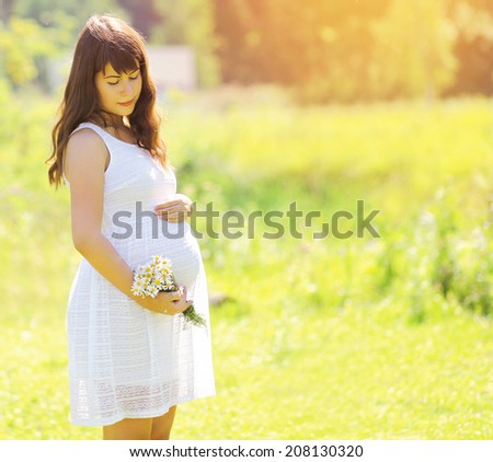 Pregnancy lovely woman in white dress with camomile flowers in summer sunny day, tender moment - stock photo