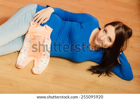 Pregnancy, motherhood and happiness concept. Pregnant woman lying on floor with clothes for the unborn baby, getting ready for the baby's arrival
