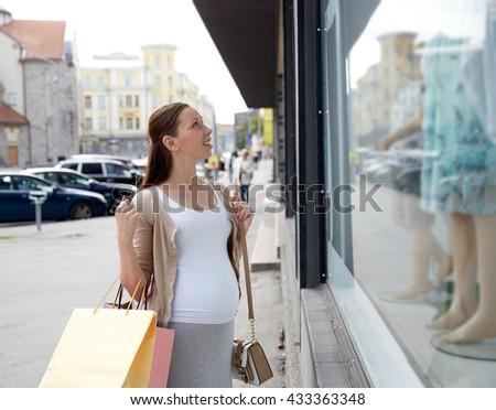 pregnancy, motherhood, people and expectation concept - happy smiling pregnant woman with shopping bags at city street - stock photo