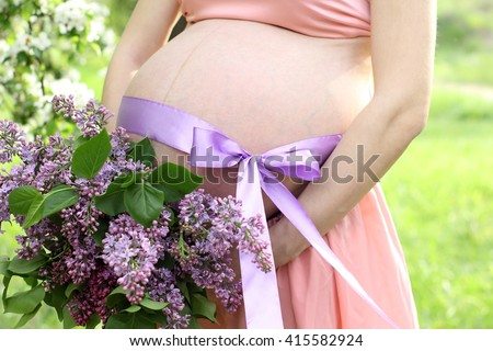 Pregnancy. Naked pregnant woman's belly. On the abdomen beautiful bow. Woman holding a bouquet of lilacs. - stock photo