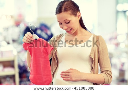 pregnancy, people, sale and expectation concept - happy pregnant woman shopping and buying baby bodysuit at children clothing store - stock photo