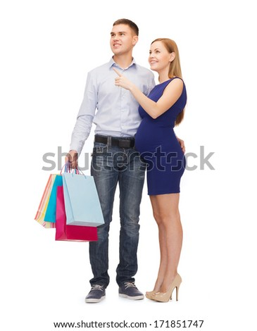 pregnancy, shopping, parenthood and happiness concept - happy young family with shopping bags expecting child pointing finger