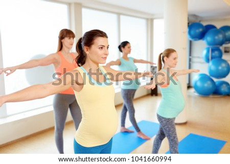 pregnancy, sport, fitness and healthy lifestyle concept - group of happy pregnant women exercising in gym