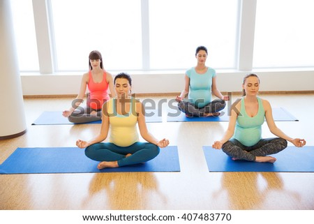 pregnancy, sport, fitness, people and healthy lifestyle concept - group of happy pregnant women exercising yoga and meditating in lotus pose in gym - stock photo
