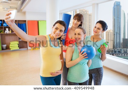 pregnancy, sport, fitness, people and healthy lifestyle concept - group of happy pregnant women with sports stuff taking selfie by smartphone in gym over city window view background