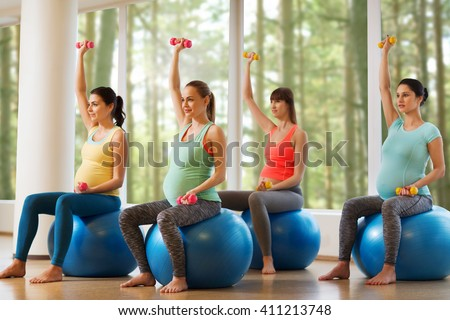 pregnancy, sport, fitness, people and healthy lifestyle concept - group of happy pregnant women with dumbbells exercising on ball in gym - stock photo
